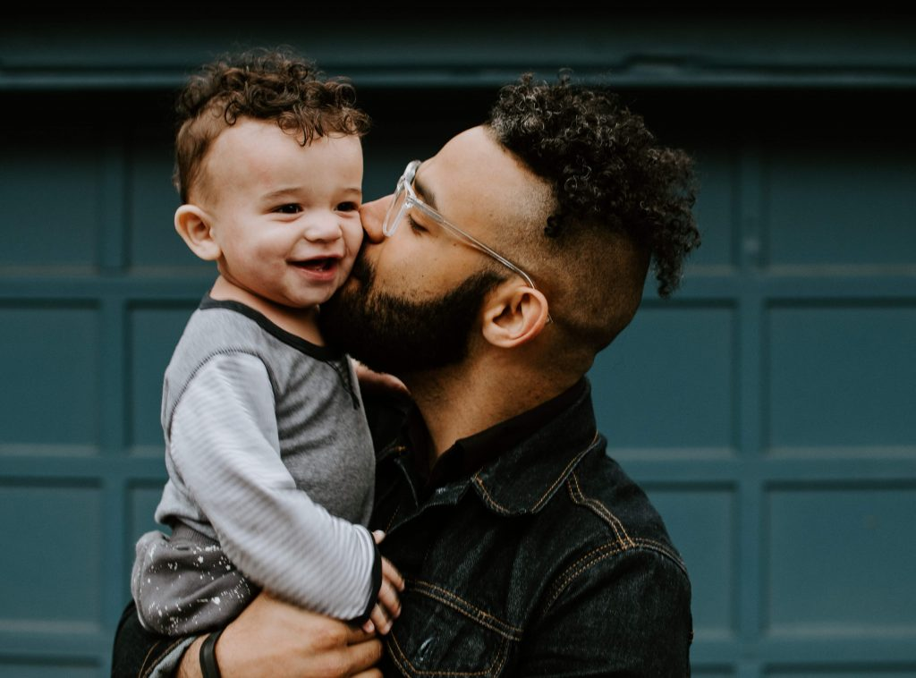 picture of a father holding his smiling baby son and kissing him on the cheek